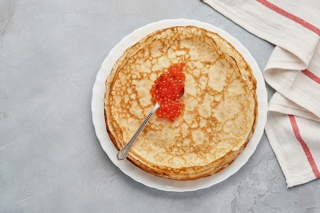 Блинчики, тонкие блины, русские блины с красной икрой на серой тарелке. мраморный фон. скопируйте пространство. вид сверху.