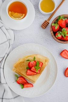 クレープ、新鮮なイチゴと明るい背景に蜂蜜と白い皿に伝統的なロシアの薄いパンケーキ。ロシアのマズレニツァ。垂直方向。上面図