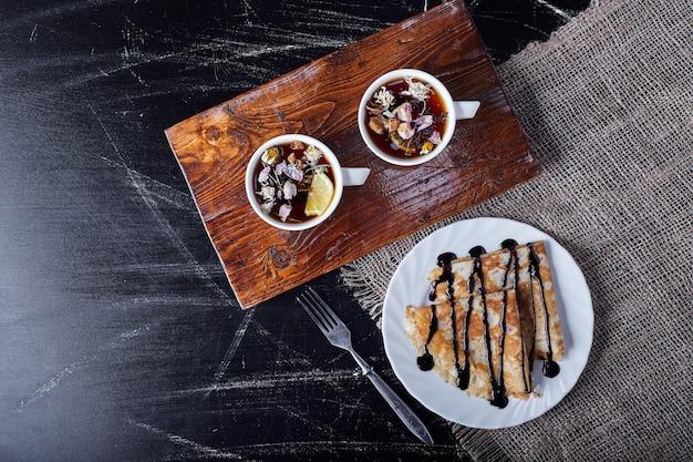 Crepes in un piatto bianco con sciroppo di cioccolato e tè.