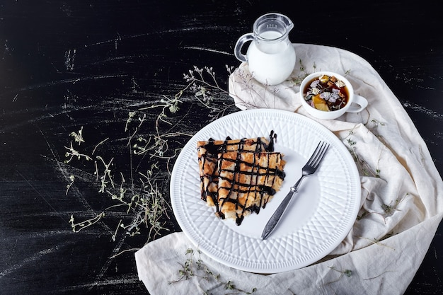Crepes in a white plate with chocolate syrup.