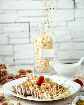Crepes with banana and strawberry, covered with milk chocolate and grated nuts