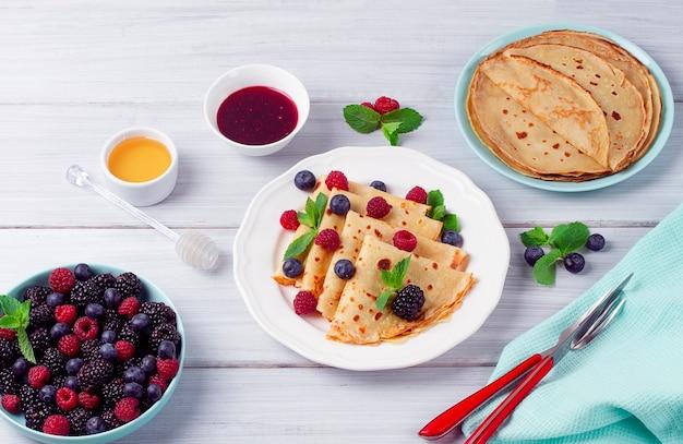 ベリーのクレープ朝食選択的に白い木製のテーブルに焦点を当てる水平方向の人はいない