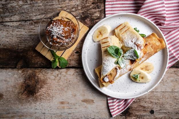 초콜릿과 바나나 크레페, 흰색 접시에 압 연