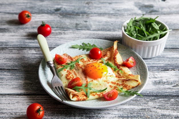 Crepes with eggs, cheese, arugula leaves and tomatoes
