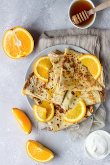 Crepes with orange, honey and natural yogurt or sour cream. thin pancakes.