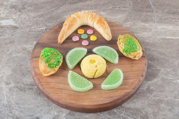 Булочка в виде полумесяца рядом с желейными конфетами, печеньем и небольшими булочками на доске на мраморной поверхности