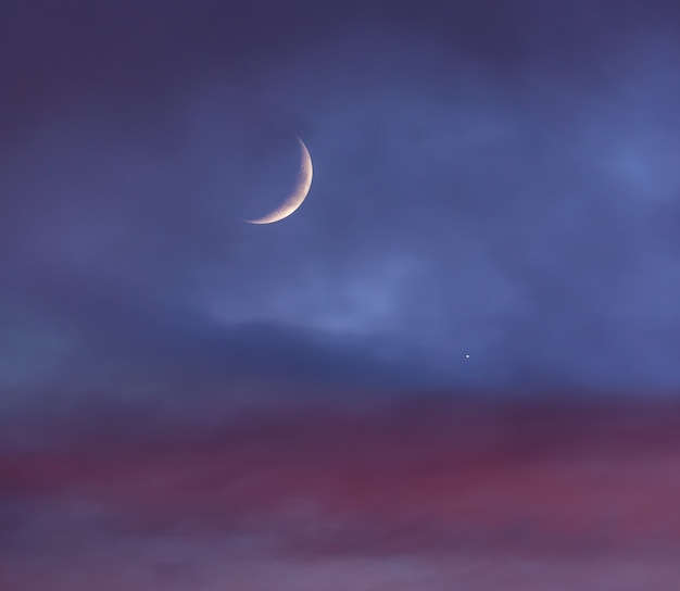 Crescent moon over the cloudy sky at sunset next to venus
