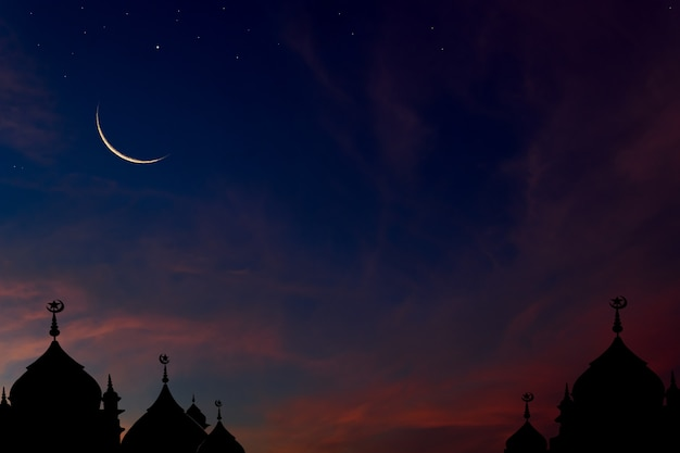 Crescent moon on dark blue dusk sky over mosques dome background