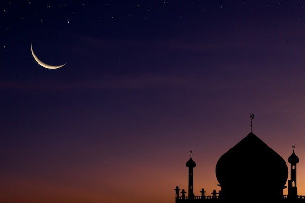 Crescent moon on dark blue dusk sky over mosques dome
