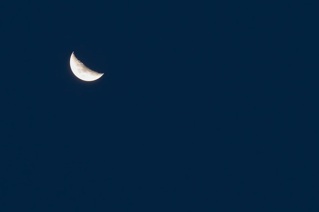 Crescent moon over midnight blue sky background