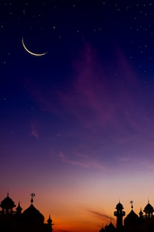 Crescent moon on twilight sky on sundown with sunlight over dome mosques