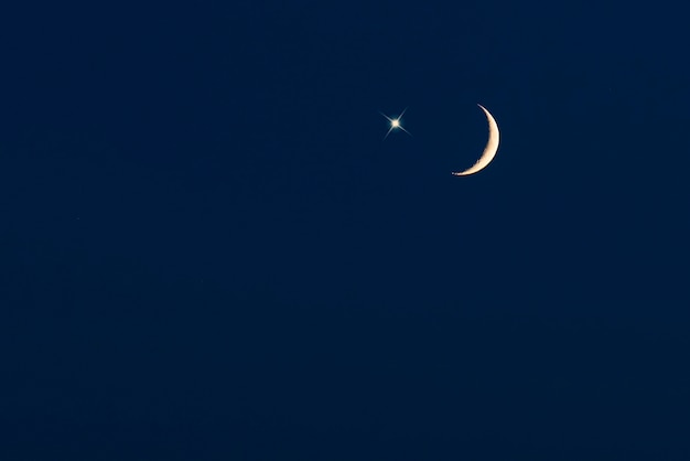 Crescent moon with star on dark-blue sky, picture for ramadan or ramazan background
