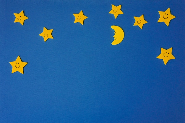 Crescent moon and yellow stars against the blue night sky.