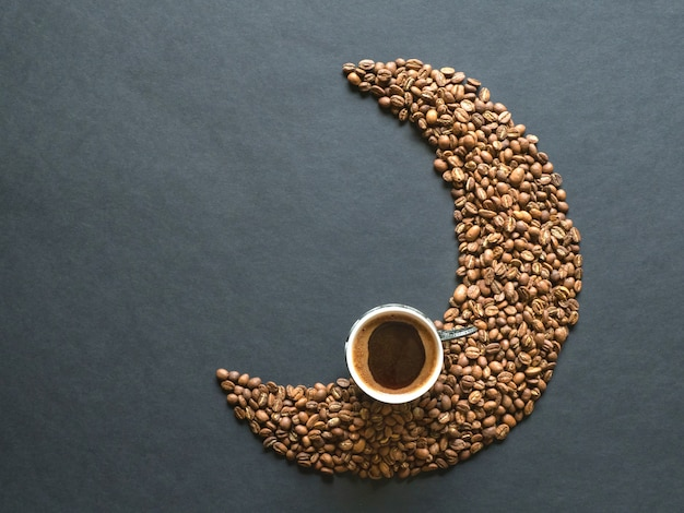 Crescent shape made of coffee beans and a cup of black coffee . top view.