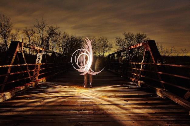 夕暮れ時に金属製の橋の上で三日月形の白い光が輝きます