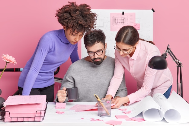 Crew of diverse skilled women and man coworkers share ideas while making future project focused at papers pose together at desktop cooperate for common task have attentive gazes. teamwork concept