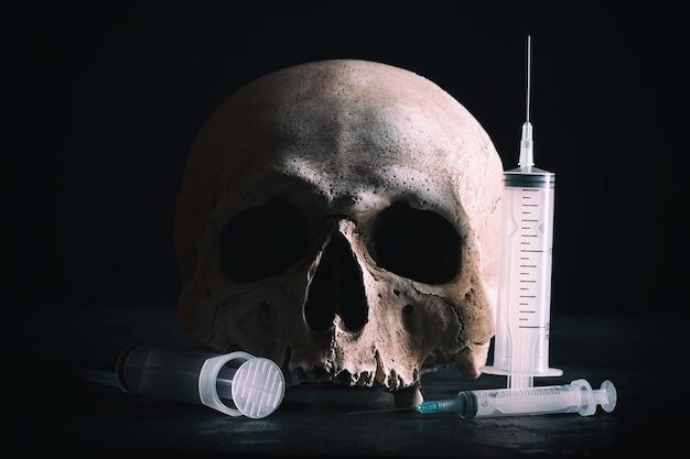 범죄와 마약 개념입니다. 어두운 배경에 주사기와 인간의 두개골입니다.