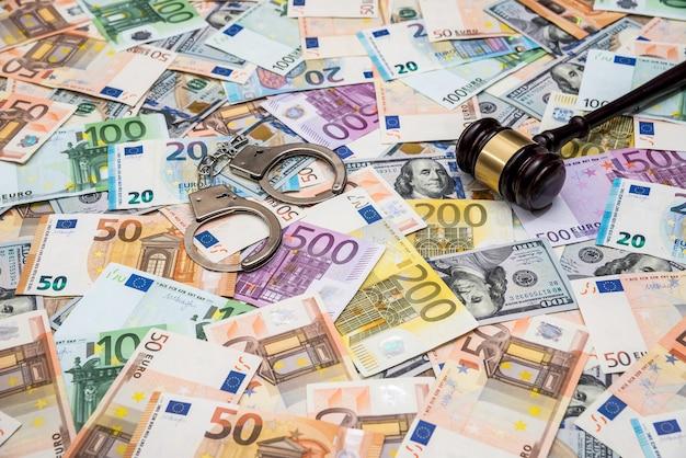 Наручники концепции преступности, молотковый доллар и банкноты евро