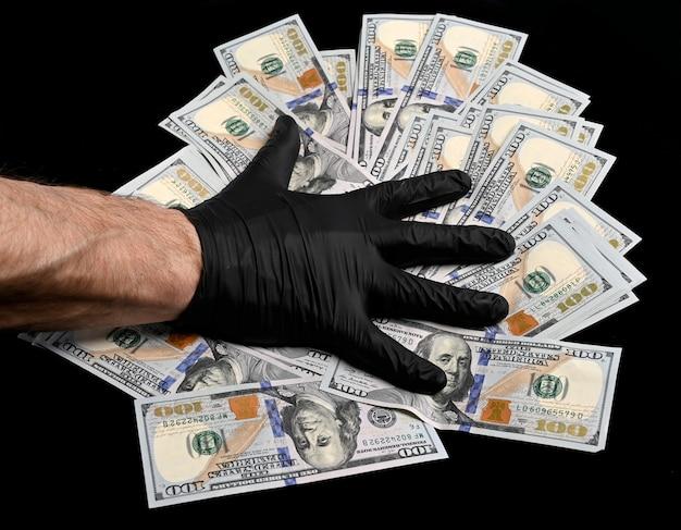 Crime concept.  man in black gloves putting hands on a pile of us dollars over black background