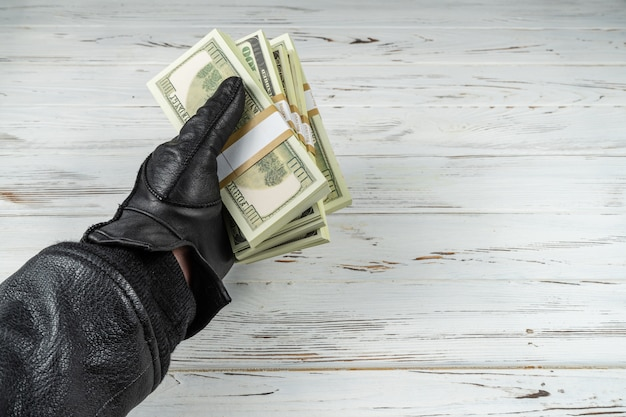 Crime concept man in black leather gloves holding bricks of money