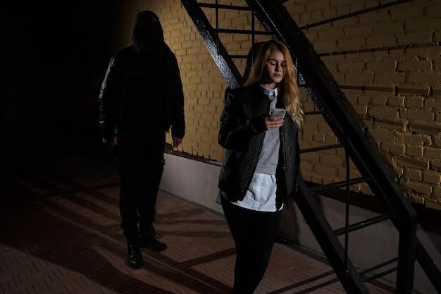 Концепции преступности концепции грабежа грабитель нацелил свой острый нож на женщину, чтобы украсть ее ценные вещи в сумке