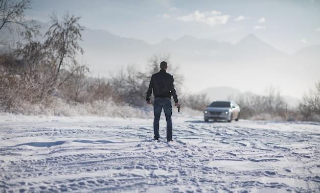 Преступник мужчина с пистолетом на открытом воздухе зимой