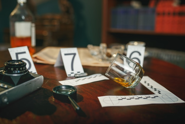 Crime scene, evidence with numbers on the table closeup, nobody. detective investigation concept, magnifying glass and retro photo camera, vintage style room interior on background