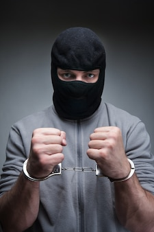 Criminal in black mask with handcuffs over grey