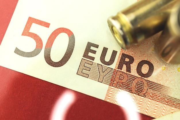 Фон концепции преступной европы с банкнотами евро и пулей для пистолета, пистолетного патрона на деньгах