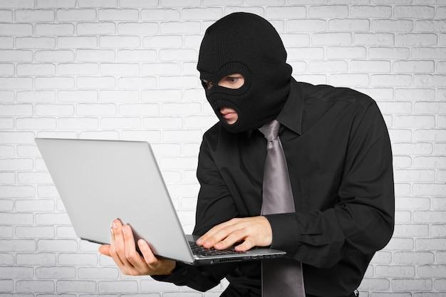 Criminal hacker wearing balaklava with laptop on brick wall background