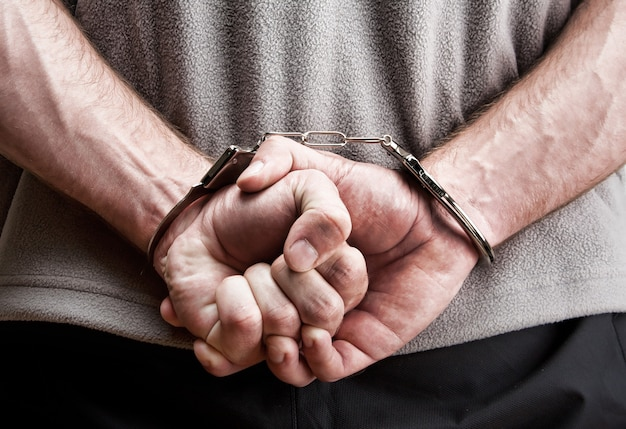 Criminal hands locked in handcuffs. close-up view