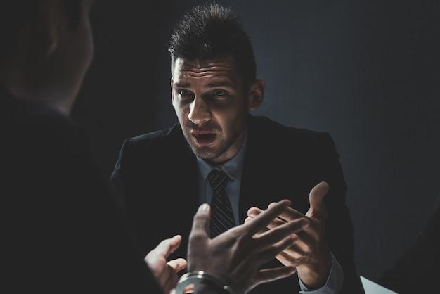 Criminal man being interviewed in interrogation room