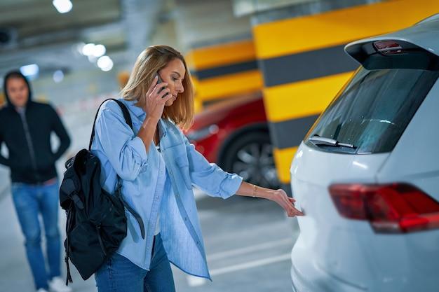 Преступник в черной толстовке с капюшоном стоит и смотрит на молодую женщину, открывающую машину на парковке