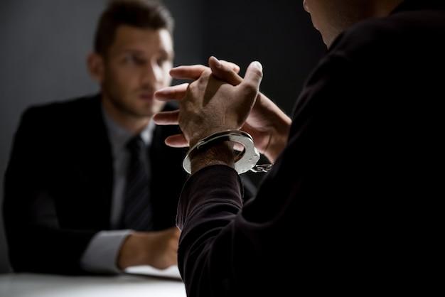 Criminal man with handcuffs being interviewed in interrogation room
