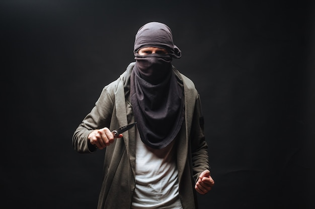 Criminal in a mask threatens with a knife the dark background