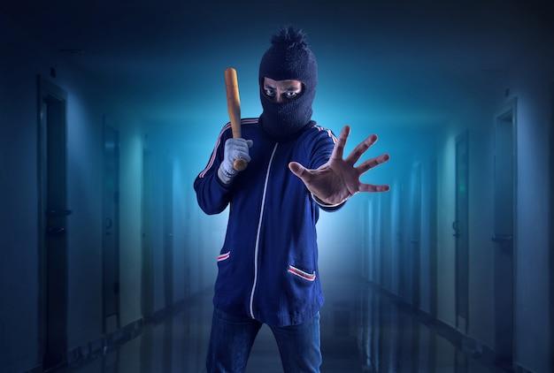 野球のバットを握る犯罪者または盗賊。