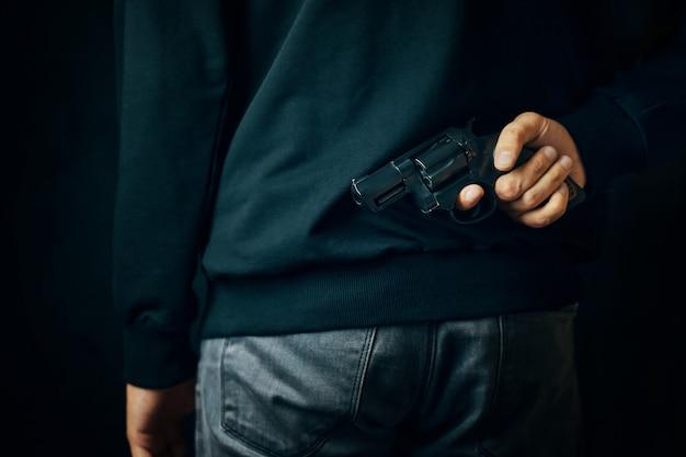 리볼버를 등에 메고 어두운 옷을 입은 범죄자가 방어를 위해 총기를 들고 있거나...