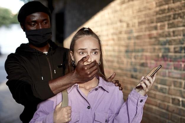 暗い通りの路地で一人で女性をストーカーし、口を閉じて、沈黙を守るように頼む。マスクをしたアフリカ系アメリカ人の男が犯罪を犯しています。おびえた女性は目を大きく開いて立っています