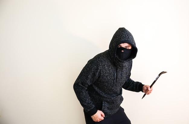ドアの近くにバールを持った犯罪者。暗いパーカーの強盗。