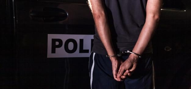 Преступник в наручниках перед полицейской машиной.