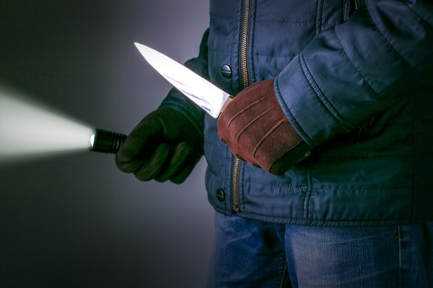 A criminal with a knife weapon threatens to kill. crime concepts robbery concepts