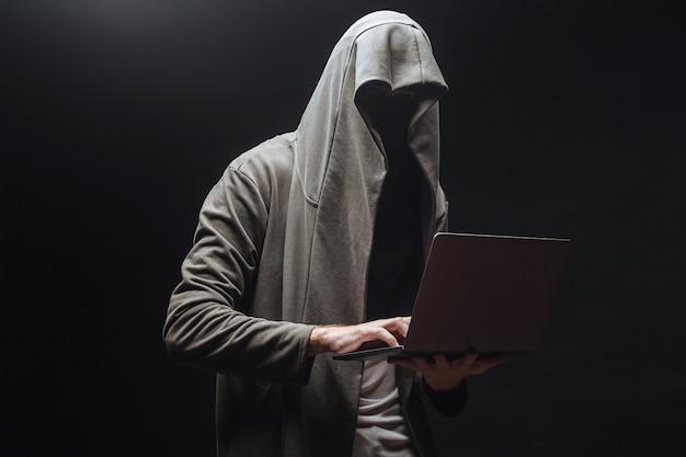 Преступник с ноутбуком в капюшоне ночью