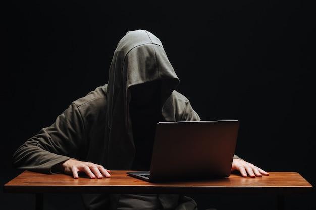 Преступник с ноутбуком в капюшоне на черном фоне