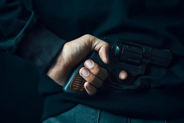 어두운 옷을 입은 남자가 등에 리볼버가있는 범죄자는 방어 또는 공격 살인자를 위해 총기를 들고 있습니다.