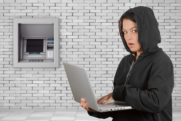 Criminal woman hacker wearing hood on using a laptop in front of build in bank cash atm machine extreme closeup.