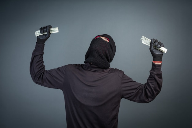 Criminals wear black masks to hold dollar cards on gray
