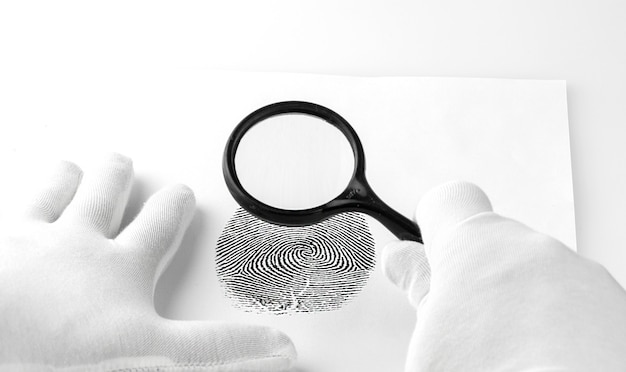 Criminology expert through a magnifying glass looking at a fingerprint.