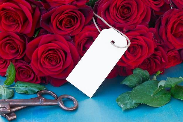 空のタグが付いている青いテーブルの上の深紅色のバラ