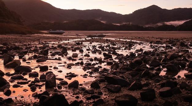 Малиновый закат в тропической бухте с заброшенной лодкой абель тасман новая зеландия