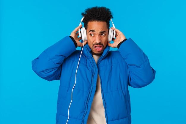 Скрипит и надоедает афроамериканец, морщась, слышит плохое качество звука наушников, не любит наушники для взлета песни и выражает неудовлетворенное выражение, противная голубая стена